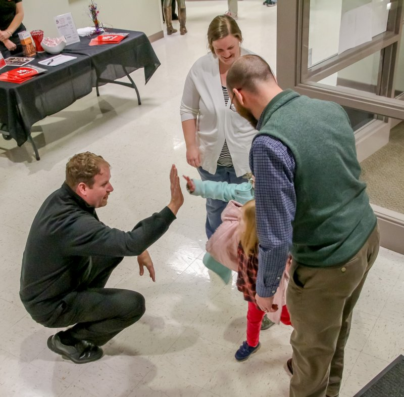 """Father Jason Gries, pastor of Holy Redeemer Parish in Evansville, high-5s a prospective student as he greets her and her parents during the Jan. 30 """"Come and See"""" event at the school. The Diocese of Evansville's 26 Catholic schools welcomed prospective families during the event, held as part of National Catholic Schools Week. The Message photo by Tim Lilley"""