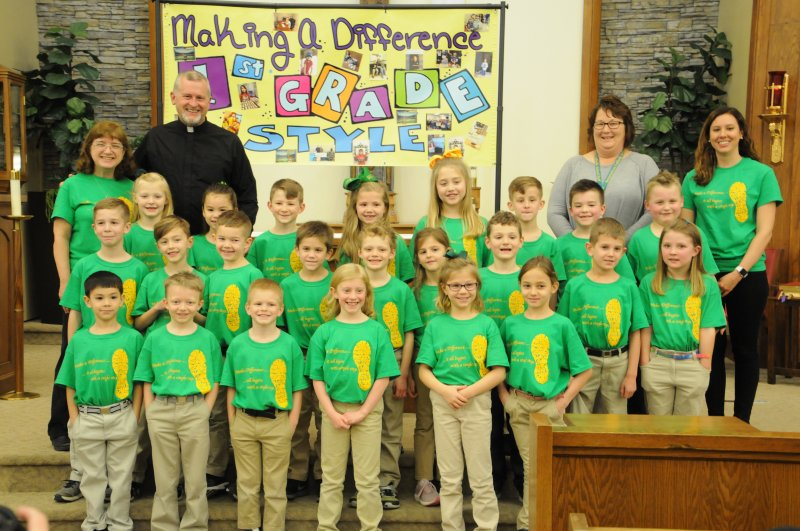 """Resurrection first-graders pose in front of the traditional """"Making a Difference 1st Grade Style"""" poster. Standing in the back row are first-grade teacher Jennifer Schmitz, left, Father Jerry Pratt, Principal Theresa Berendes, and first-grade teacher Jennifer Meyer. The Message photo by Megan Erbacher"""
