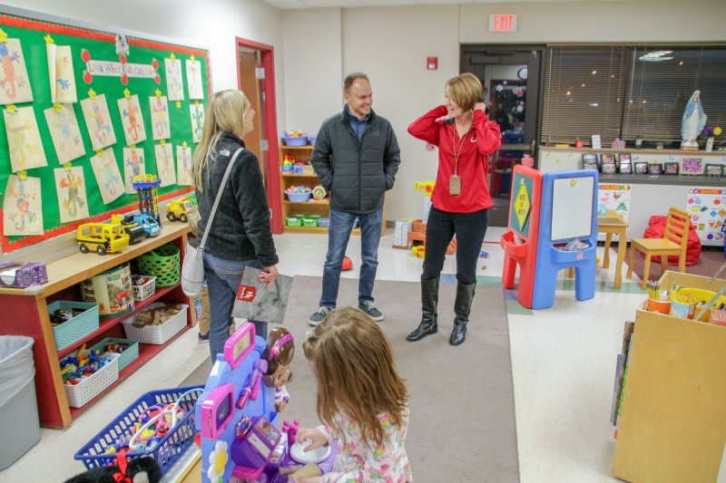 Holy Redeemer Preschool Director Amy Daunhauer, in red, visits with a prospective family. The Message photo by Tim Lilley