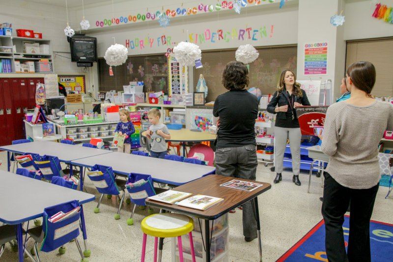 Holy Redeemer Kindergarten Teacher Caroline Raley facing the camera, discusses Holy Redeemer School with prospective families. Joining her, in the black shirt facing away from the camera is Holy Redeemer resource teacher/counselor Christan Shockley. The Message photo by Tim Lilley