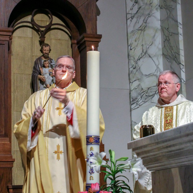 St. Benedict Cathedral Rector Benedictine Father Godfrey Mullen watches Bishop Joseph M. Siegel light the Paschal Candle at the beginning of the April 11 Easter Vigil Mass at the cathedral.