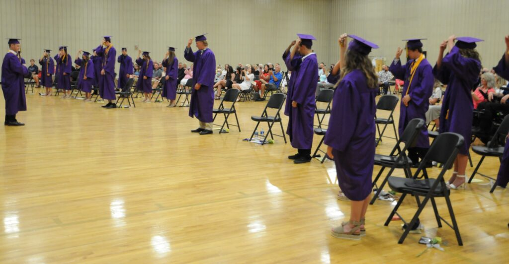 Rivet High School Class of 2020 President Noah Donovan, far left, leads his peers as they move their tassels to signify their status as high school graduates. The Message photo by Megan Erbacher