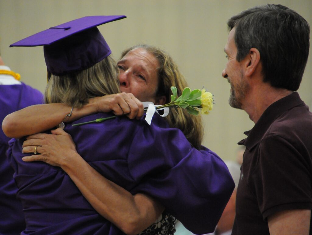 Rivet graduate Bella Atkinson hugs her mother Sabrina Atkinson-Dornhoefer, middle, as her father John looks on with a smile. Bella joined her classmates in presenting flowers and hugs of gratitude to their parents during Commencement. The Message photo by Megan Erbacher
