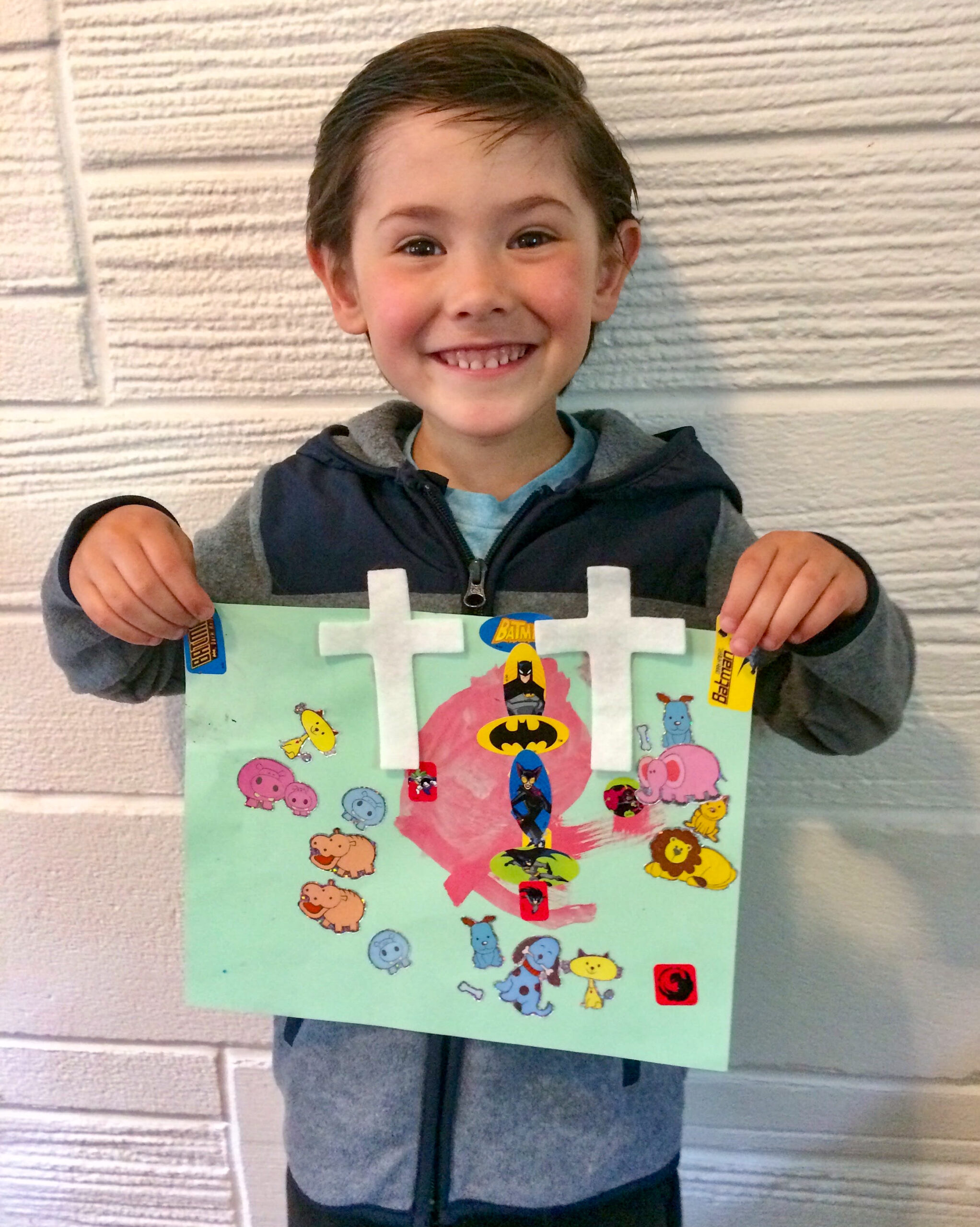 """Diocese of Evansville Deacon Tom Cervone sent us this photo of his grandson, Henry Gish, 4, with the poster he created for his bedroom during the COVID-19 stay-at-home restrictions. He shares the bedroom with his sister, Amerlia, 2. Deacon Tom told us, """"Henry told hismom and dad that theposter had to have Jesus, hippos, dogs and Batman. I love his mindset."""" Henry is a Pre-K student at Sts. Peter and St. Paul School in Haubstadt. He is the son of John and Nicole Gish; John teaches at Sts. Peter and St. Paul. Grandparents are Deacon Tom and Marie Cervone, and Mark and Jenny Gish. Well-done Henry! Submitted photo courtesy of Deacon Tom Cervone"""