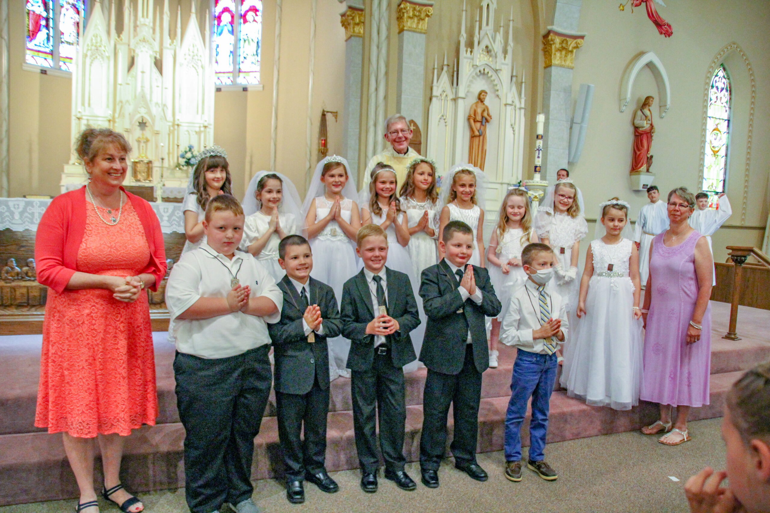 St. John the Evangelist Parish in Loogootee celebrated First Communion for 14 second-graders during the 6 p.m. Mass on June 5. Shown are Catechist Kim Bowling, front row left, Wade George Curtis Sheetz, Holden O'Neil Lingenfelter, Liam Marshall Kluesner, Ashton Thomas Summers, Isaac Alan Lagree, Catechist Paula Ringwald, Mary-Grace Catherine Todd, second row left, Skylyr Vera Ann Raney, Landry Deane Louise Strange, Fara Kate Fisher, Kensleigh Izabelle Carrico, Brylee Korynn Bateman, Olivia Jean Padgett, Clare Isabel Ringwald and Eva Grace Ringwald, St. John the Evangelist Pastor Father Kenneth Walker is standing behind the group. Student Lucy Rahman was unable to attend. She will make her First Communion at a later date. Submitted photo