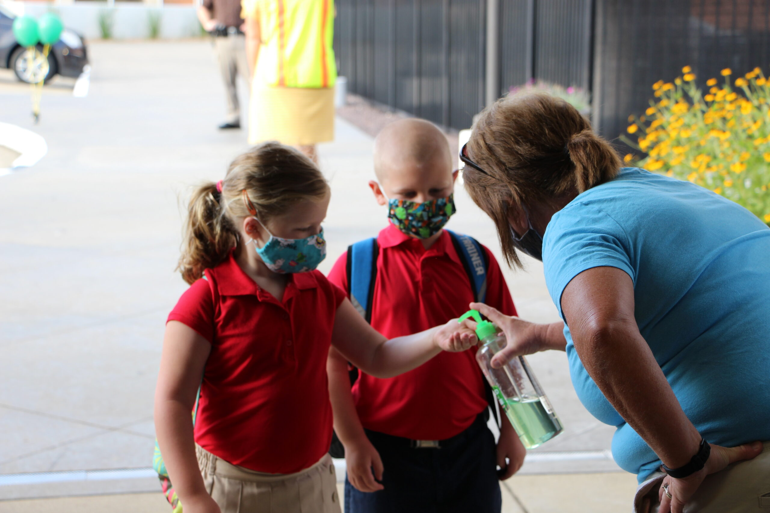 Resurrection School students Jackie Aldridge and Augi Wilson get hand sanitizer as they enter the building Aug. 6, the first day of school for the 2020-21 school year.