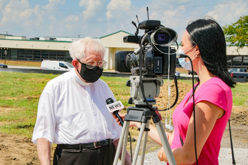 Father Ted Tempel speaks with Eyewitness News reporters Joylyn Bukovac during the Aug. 10 blessing and groundbreaking for St. Theresa Place. The Message photo by Tim Lilley