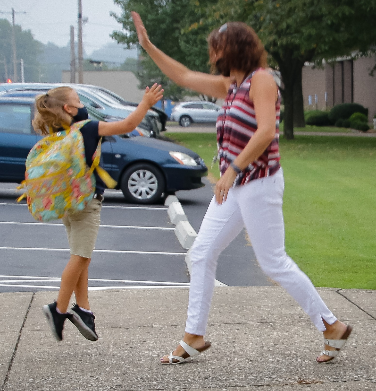First-grader Charlotte Mosbey, left, greets Holy Redeemer School principal Andrea Dickel as she arrives for school on Sept. 11. Dickel has been holding Friday morning dance parties to welcome students to school. Many students join her for a quick dance when they arrive, but Charlotte opted for a high five! The Message photo by Tim Lilley
