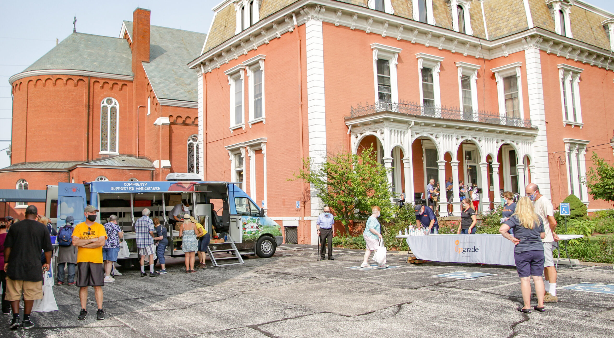 Neighbors of All Saints Parish's St. Anthony Campus in Evansville move through the line to get fresh produce during the parish's final 2020 produce giveaway, held Sept. 13. At right, members of the parish's praise band perform from the porch of the rectory. Approximately 30 individuals and families made it through the line during the first five minutes – a testament to the popularity and success of this effort, made possible by All Saints Parish and Seton Harvest of Evansville. The Message photo by Tim Lilley