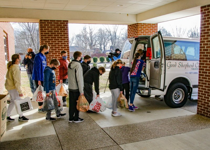 "Local media photograph and shoot video of Good Shepherd School students on Feb. 5 as the youngsters load some of the 3,300 items they collected the week of Feb. 1 to benefit the St. Vincent de Paul food pantry in Evansville. Principal Kristen Girten tells The Message that students also collected more than $3,400 in cash donations to benefit the SVdP food pantry. The school holds an annual competition among grades to collect food and donations for the pantry. This year, Girten and the staff scheduled the competition to coincide with the national observance of Catholic Schools Week. One grade annually wins the competition; and this year, for the first time, the title went to the ""Class of 2021"" – the eighth grade. Congratulations! The Message photo by Tim Lilley"