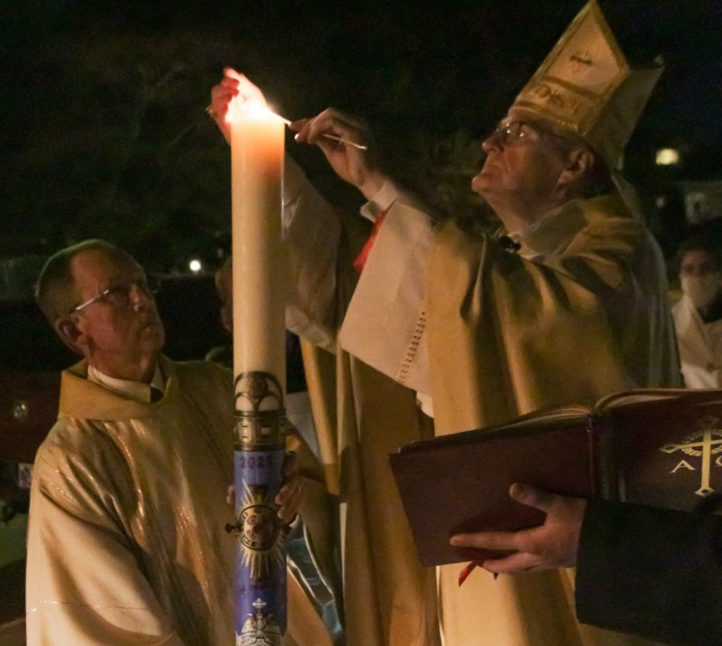 Bishop Siegel lights the Paschal Candle, being held by Deacon David Rice, outside the Cathedral at the beginning of the vigil. The Message photo by Tim Lilley