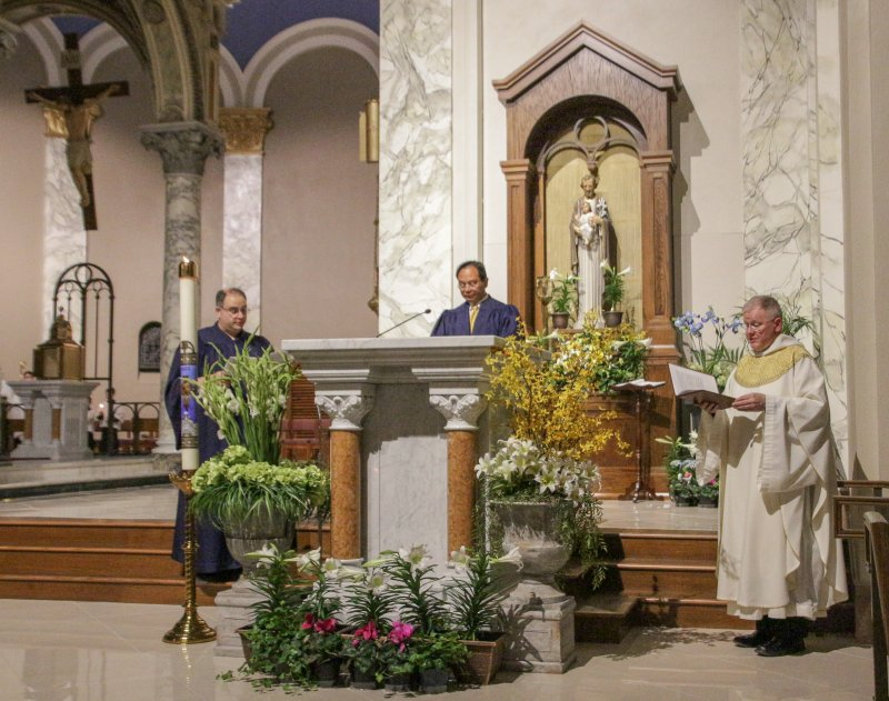 Cathedral Director of Music Jeremy Korba, left, parishioner Mark Valenzuela and Benedictine Father Godfrey Mullen, rector of the cathedral, sing the Easter Proclamation (Exsulset) as the Mass begins. The Message photo by Tim Lilley