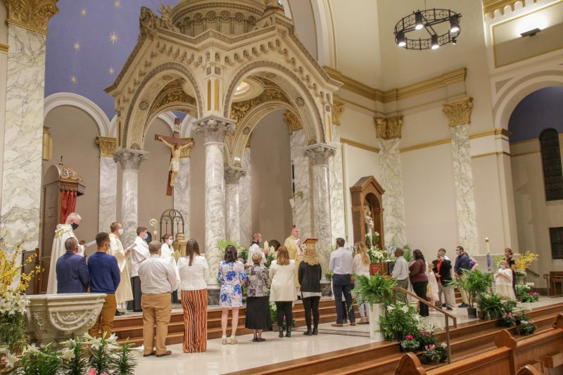 Bishop Siegel prays with those accepted into full communion and their sponsors during the Mass. The Message photo by Tim Lilley