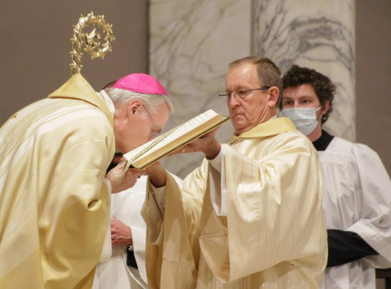 Bishop Siegel kisses the Book of the Gospels following Deacon David Rice's reading of St. Mark's account of the Resurrection (Mark 16: 1-7). The Message photo by Tim Lilley