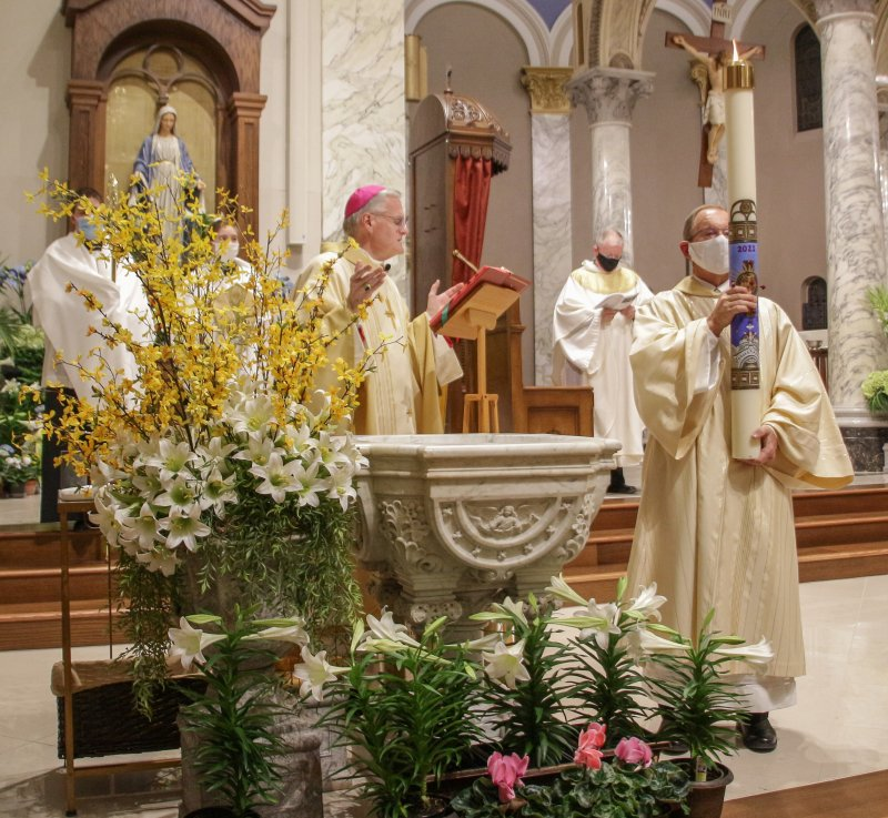 Bishop Siegel blesses the baptismal water. The Message photo by Tim Lilley