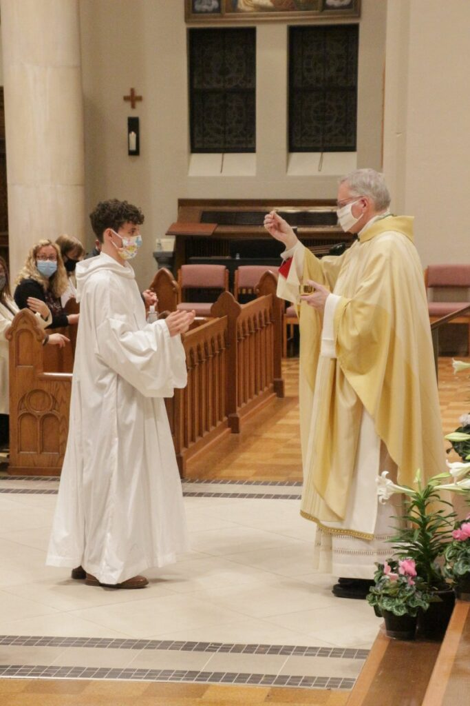 Gabriel Boeglin, who was baptized and confirmed during the Mass, receives First Holy Communion from Bishop Siegel. The Message photo by Tim Lilley
