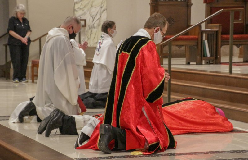 Bishop Siegel prostrates himself before the altar at the beginning of the celebration. The Message photo by Tim Lilley