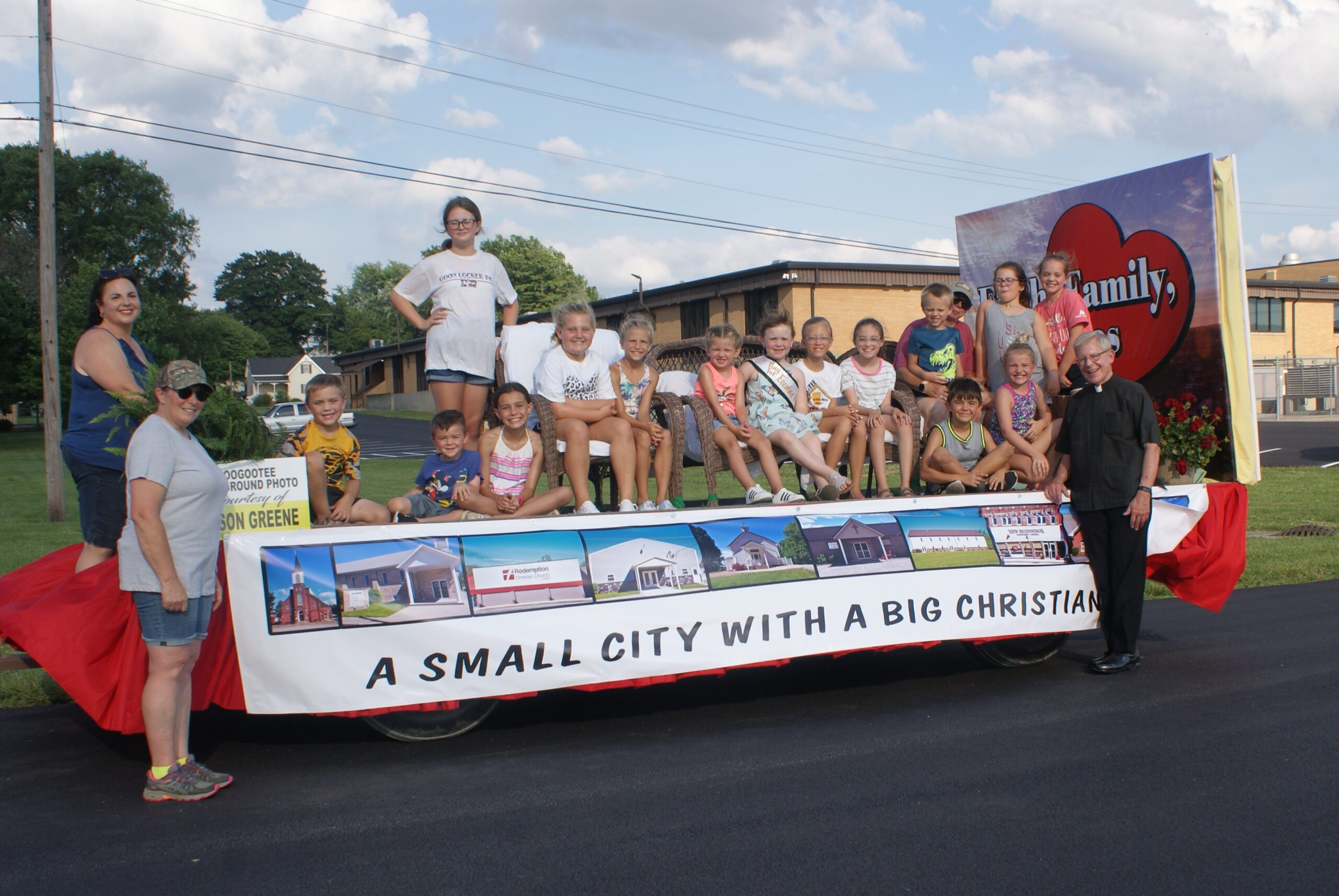 St. John the Evangelist Parish in Loogootee designed and constructed a float for the Loogootee Summerfest parade June 26. The parish is most appreciative of the efforts of parishioner Sandy Woods, whose vision, creativity and skills make the floats a major source of pride and enjoyment! Pictured are Sandy Woods, front row left, Blake Stoll, Garrett Mathies, Mason Mathies, Bella Hager, Father Kenneth Walker, pastor of St. John the Evangelist Parish in Loogootee and Diocese of Evansville Judicial Vicar, Jackie Esch, second row left, Natalie Willoughby, Hailey Thomas, Jerzie Wildman, Avrie Bratton, Bailey Esch, Zoey Harder, Avery Wagoner, Reid Johnson, Paula Ringwald, Haley Hager and Mackenzie Johnson.  Submitted photo