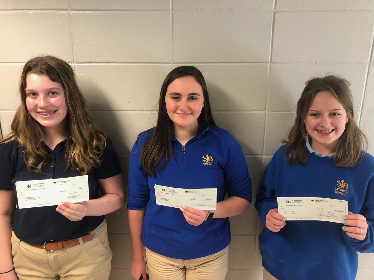 The winners of St. John the Baptist School's Eighth Grade Speech Madness competition are third-place winner Lyla Wisher, left, second-place winner Lyra Sagez and first-place winner Margaret Janney. The girls are shown holding the checks to be donated to the charities of their choice. Submitted photo