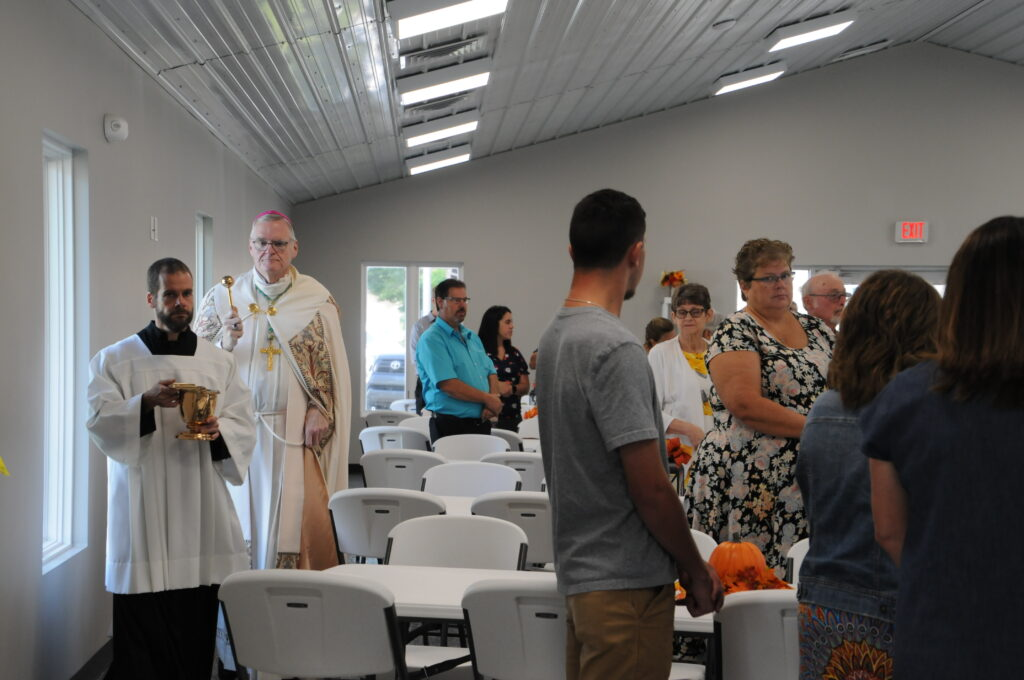 Bishop Joseph M. Siegel sprinkles holy water throughout St. Philip Neri's new parish hall during a dedication and blessing Aug. 29. Matt Miller, diocesan director of the Office of Worship, assists the bishop. The Message photo by Megan Erbacher
