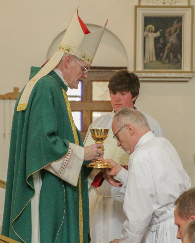 Diaconate Candidate Kevin Kilmer of St. Francis Xavier Parish in Vincennes holds the chalice used in the celebration of Mass as Bishop Siegel prays over him. The bishop repeated this for all 12 candidates. The Message photo by Tim Lilley
