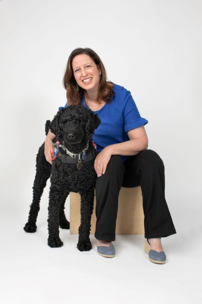 Author Michal Babay poses with real-life service dog, Chewie.