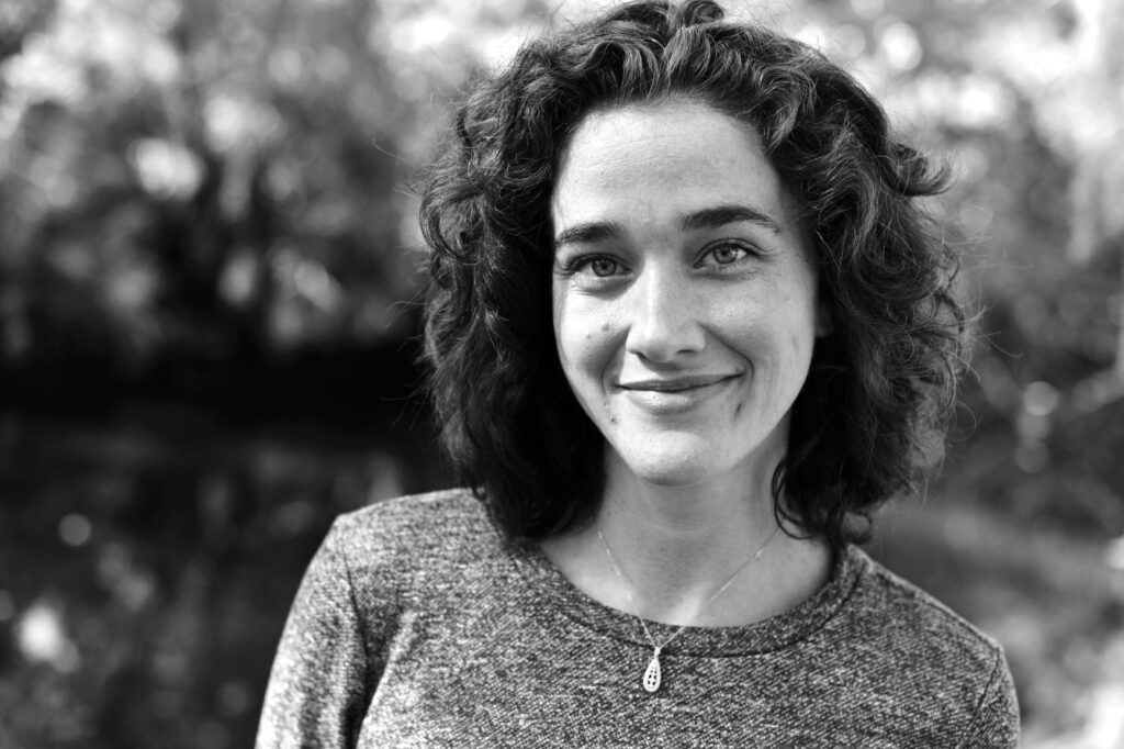 Black and white photo of author Katie Frawley: a white woman with curly brown hair.