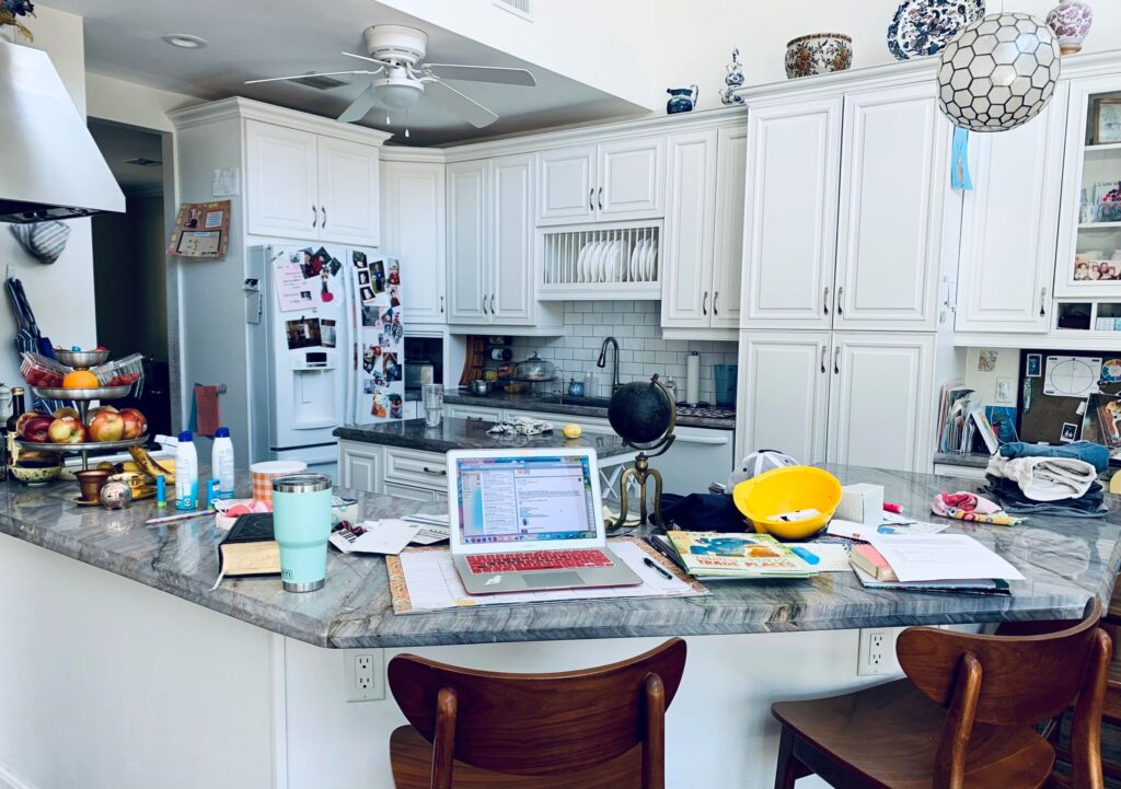 Picture of the author's workspace: a kitchen countertop with a laptop, stools, and various other items.