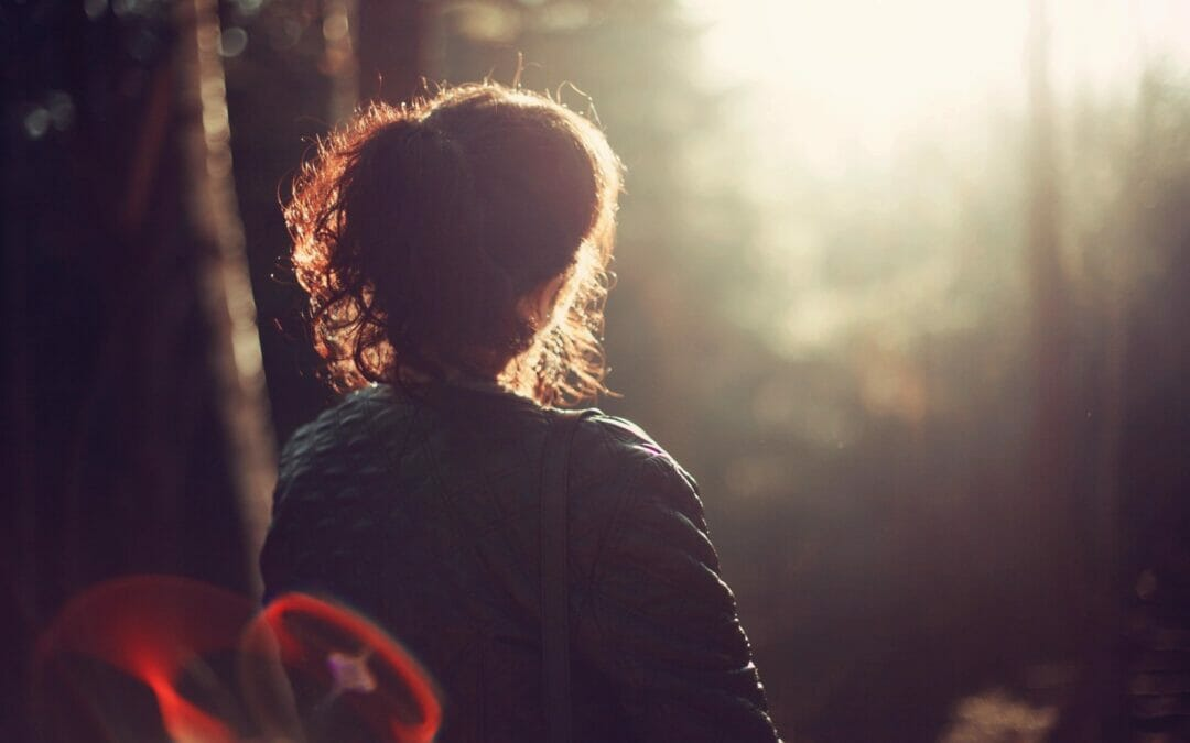 woman sitting looking towards light in forest