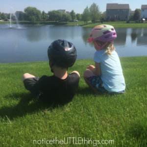 siblings sitting by a pond