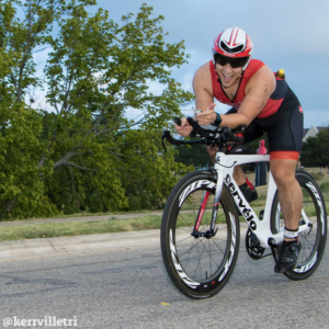 Cyclist rides in an aero position, smiling at the camera, during the 2018 Kerrville Triathlon. Credit Ed Sparks.