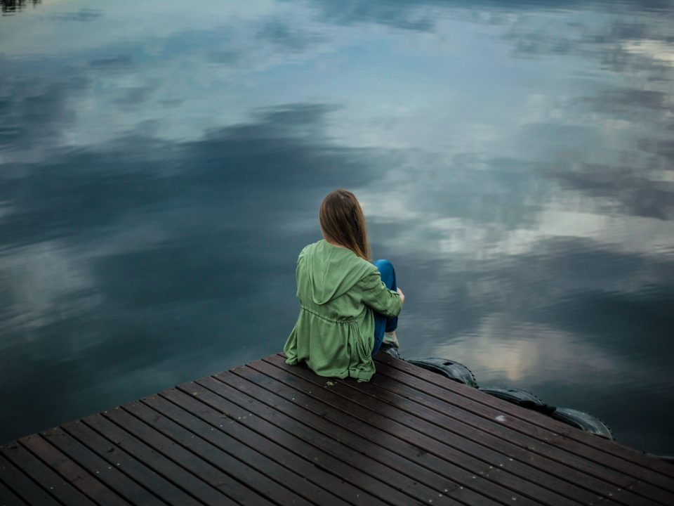 woman sitting on dock near body of water
