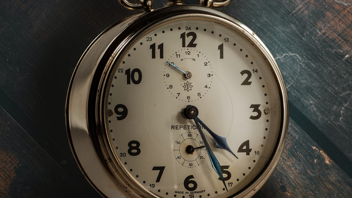 round silver and white analog desk clock pointing at 4:26