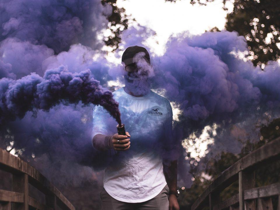 man holding purple smoke