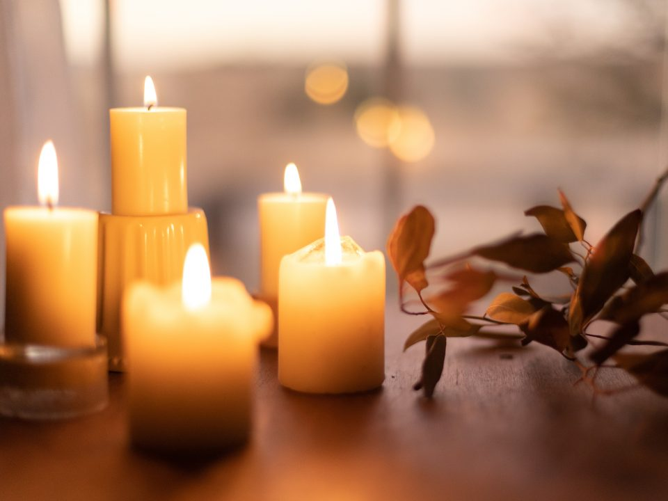 white pillar candles on brown wooden table