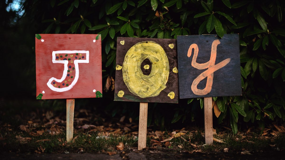 three assorted-color joy signage