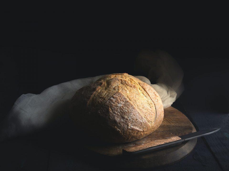 baked bread beside knife on wooden board