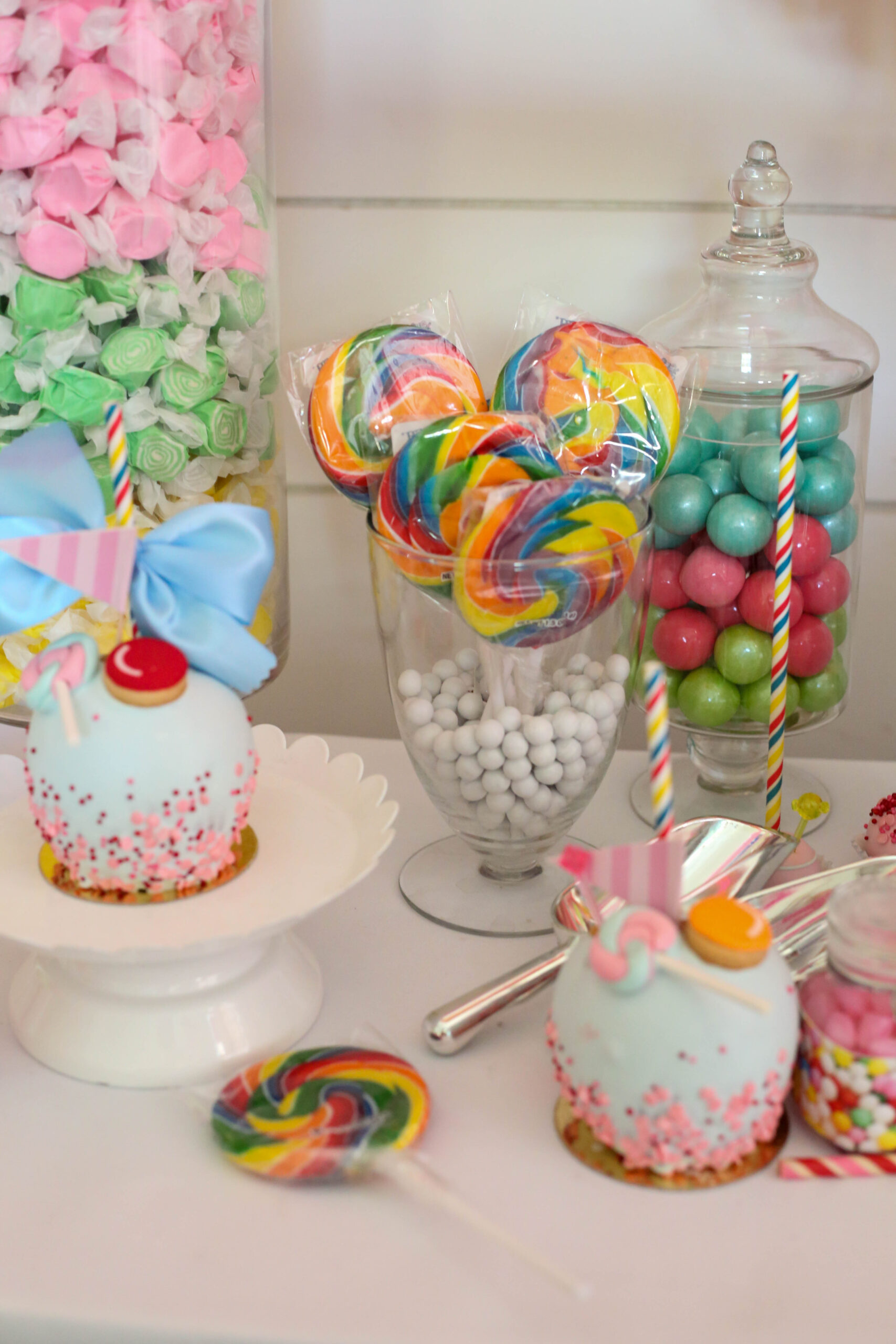candy jars in a candy buffet display with taffy, lollipops and gumballs