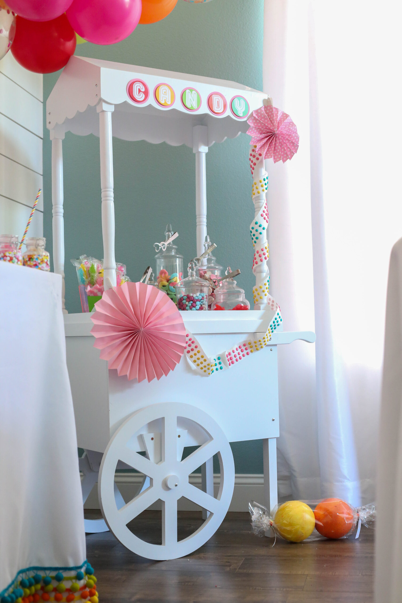 candy cart decorated for a sweet rainbow themed candy party