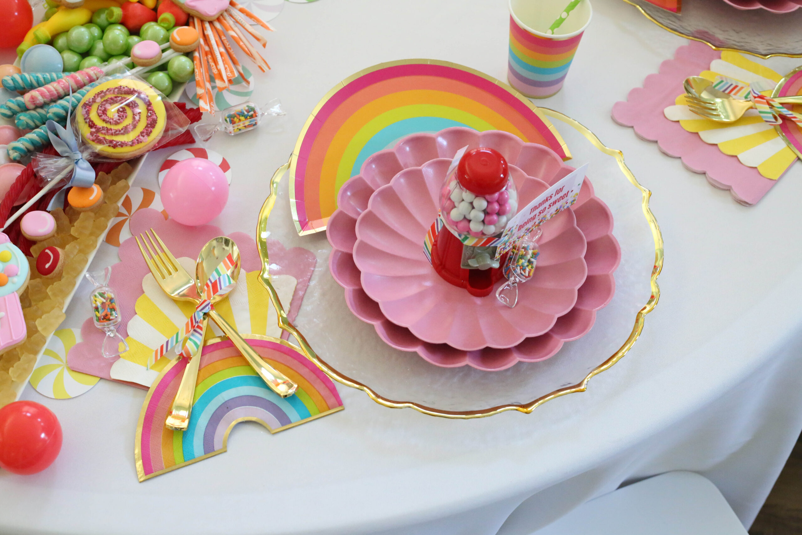 candy party place setting at a round table with a white table cloth