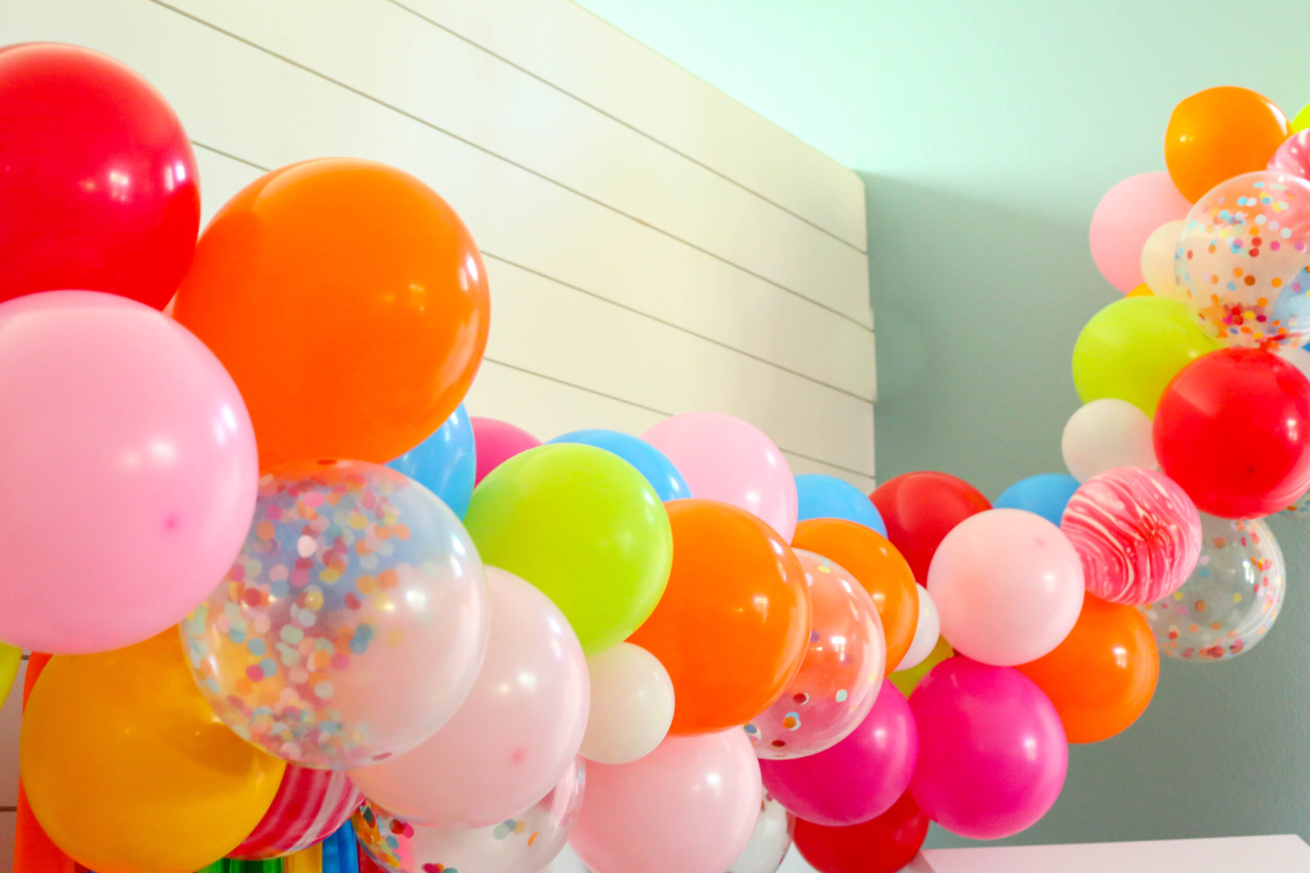 extra long balloon garland with confetti balloons and red marble balloons