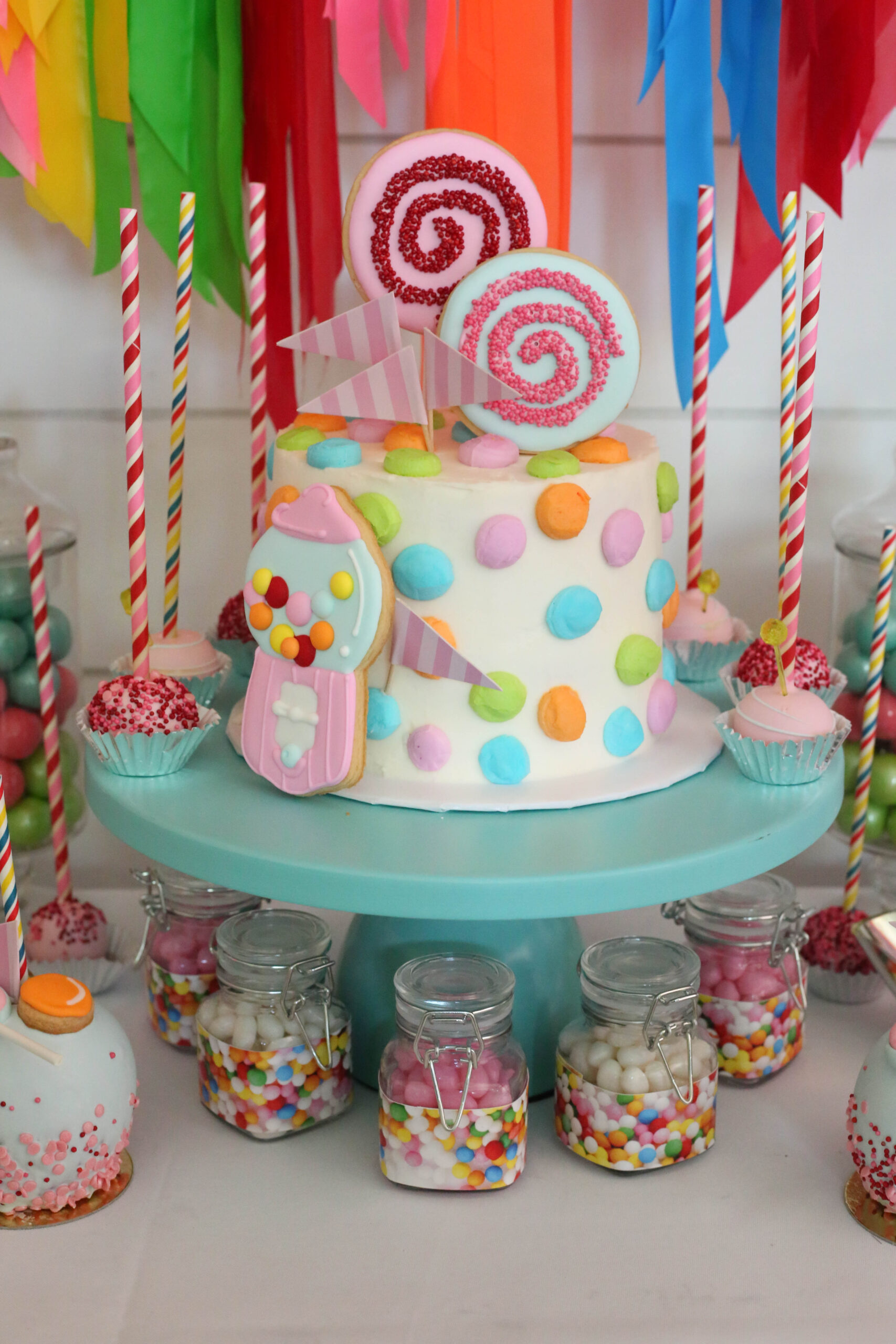 candy buttons cake and flag tape backdrop at a rainbow candy party
