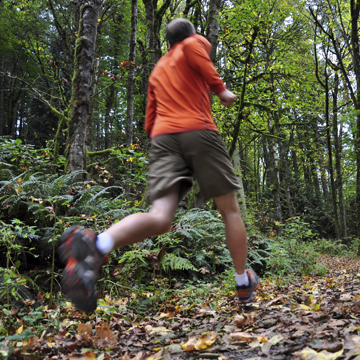 A mature man trail running in the woods.