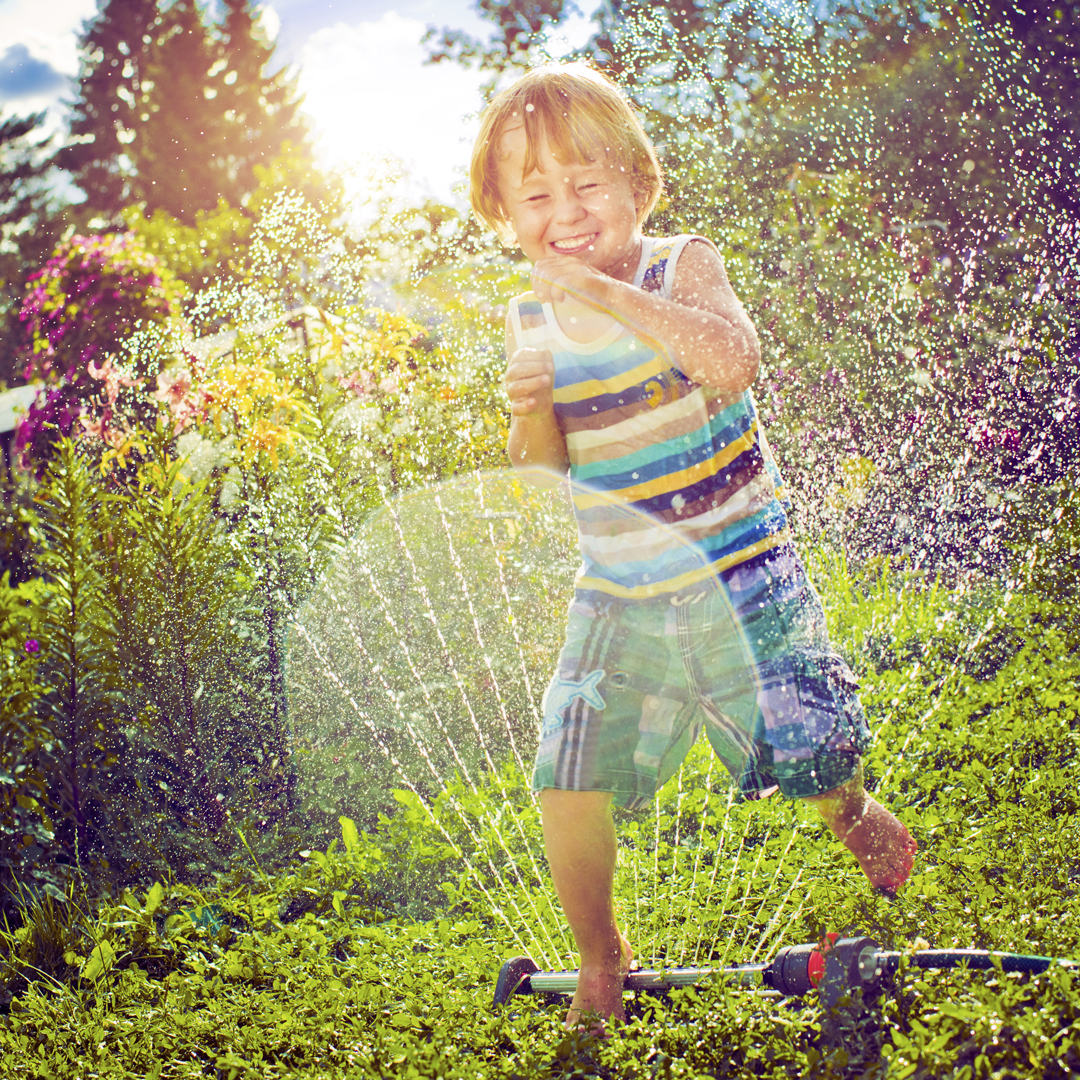 A young child plays in a sprinkler.