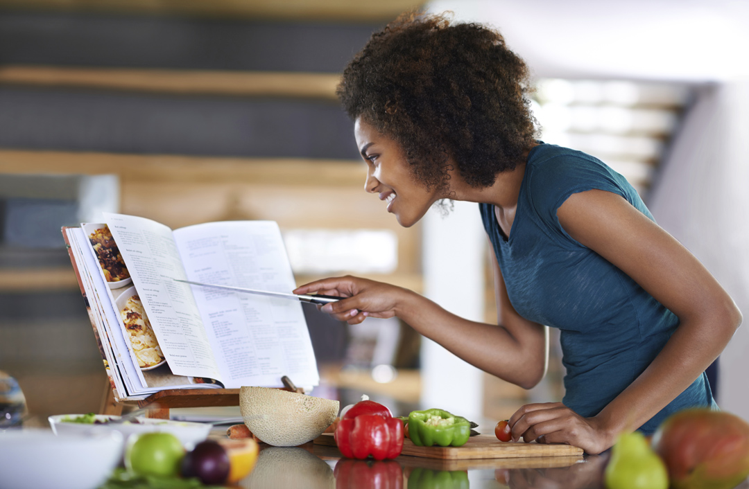 A woman enthusiastically looks at a cookbook with healthy ingredients all around her.