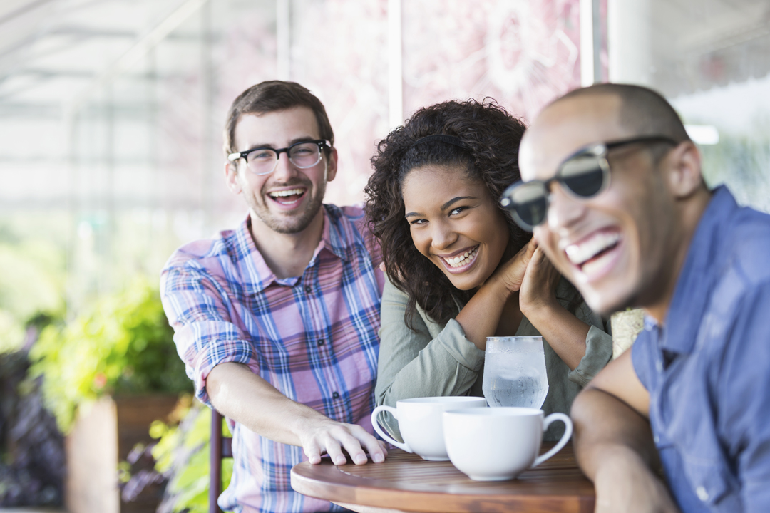 Younger group of friends smiling and having coffee at an outside table.