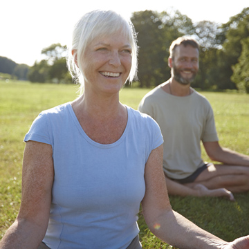 A smiling mature woman practices yoga outside.