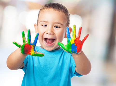 happy little boy with painted hands