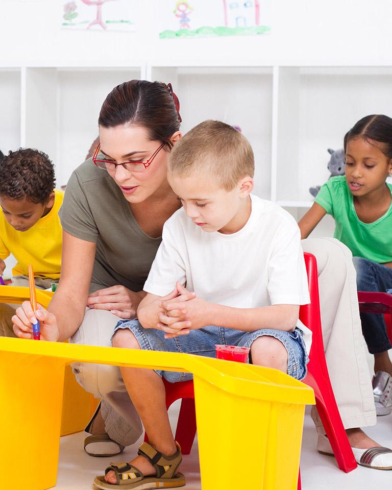 teacher helping student at desk
