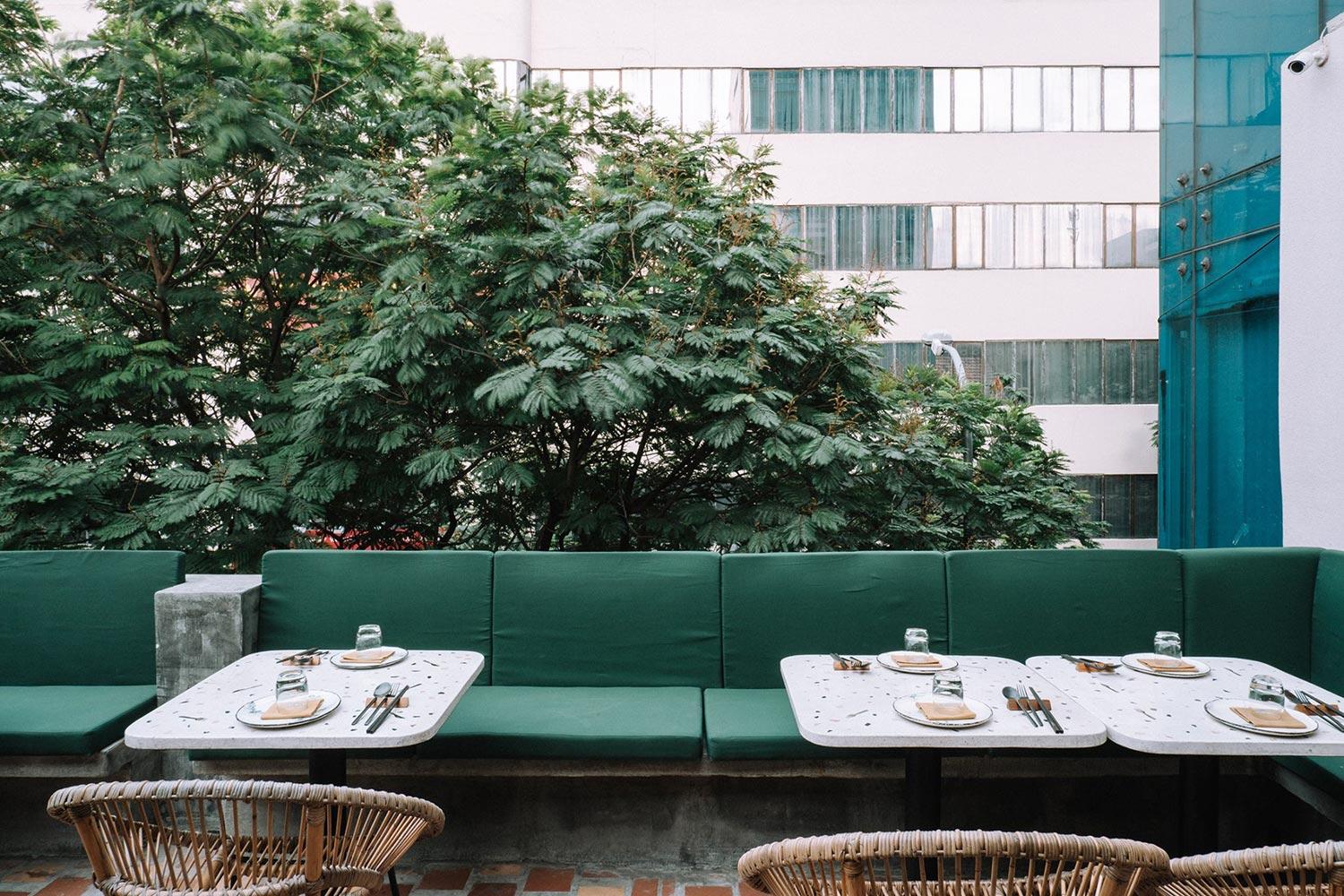 Kiba Saigon outdoor tables and sofa surrounded with trees and office building